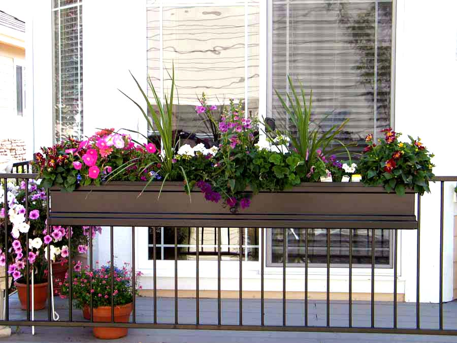 Wrought iron railing brackets suspend a beautifully planted Fiberglass Supreme window box.