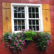 A flower box beneath a window with shutters
